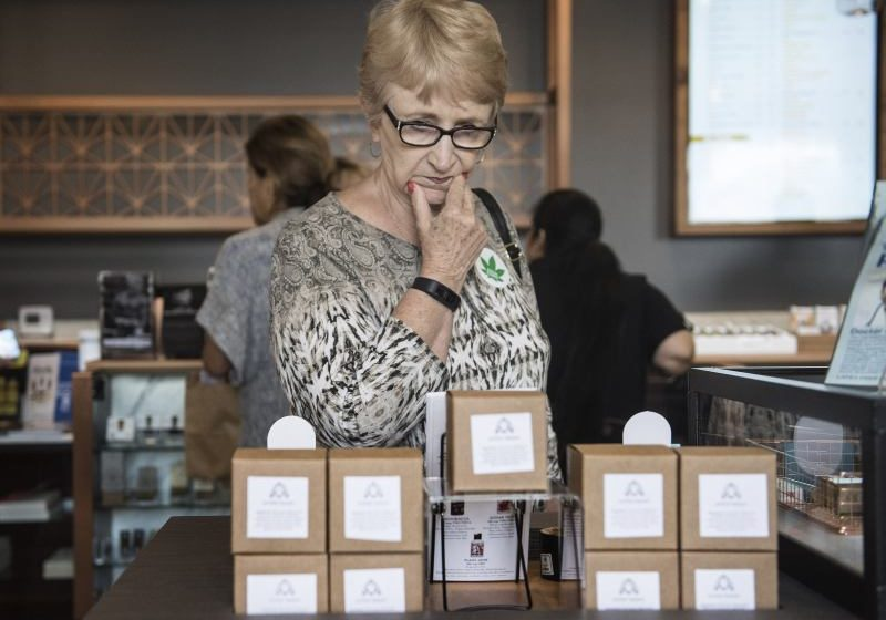 Lynn Jarrett of Laguna Woods browses the different types of medicated cannabis products for sale at Bud and Bloom in Santa Ana, on Wednesday, August 2, 2017. Jarrett had never been to a dispensary before and was looking for a solution for pain in her mouth that traditional medication was not helping. (Photo by Nick Agro, Orange County Register/SCNG)